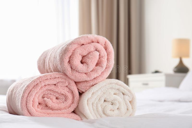 Rolled soft towels on bed in room. Space for text royalty free stock photography