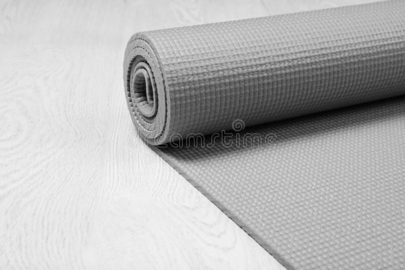 Rolled sports mat on wooden background. Space for text stock photo