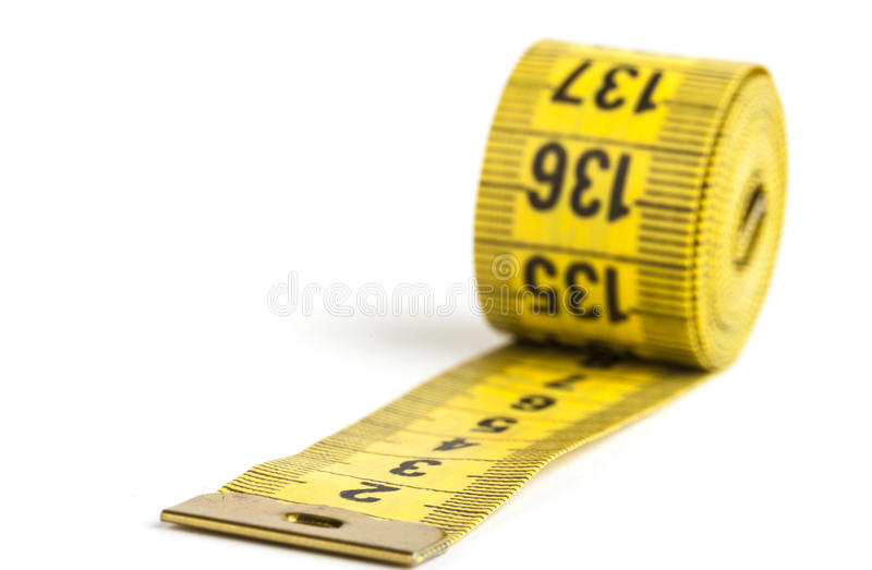 Rolled Tape. Yellow rolled up measuring tape isolated on white background royalty free stock image