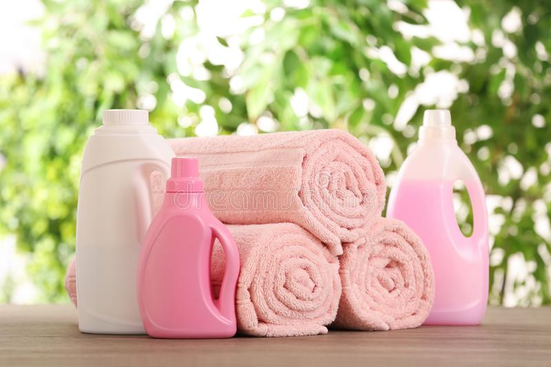 Rolled towels and detergents on wooden table. Against blurred background royalty free stock photo