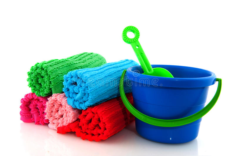 Rolled towels and playset. Colorful rolled towels from terry and play set for the beach isolated over white royalty free stock image
