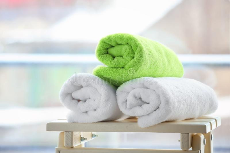 Rolled towels on table. Against blurred background stock photography