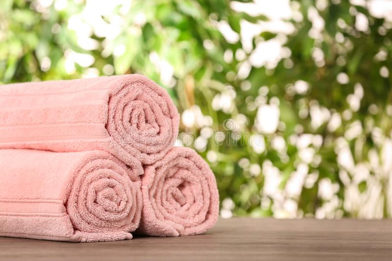 Rolled towels on wooden table against blurred background. Space for text royalty free stock photo