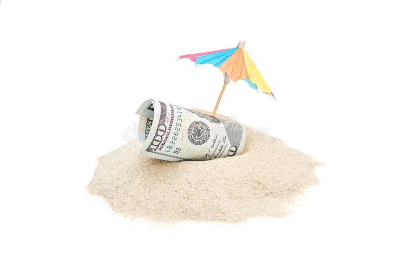 Rolled up money with beach umbrella on the heap of sand. stock image