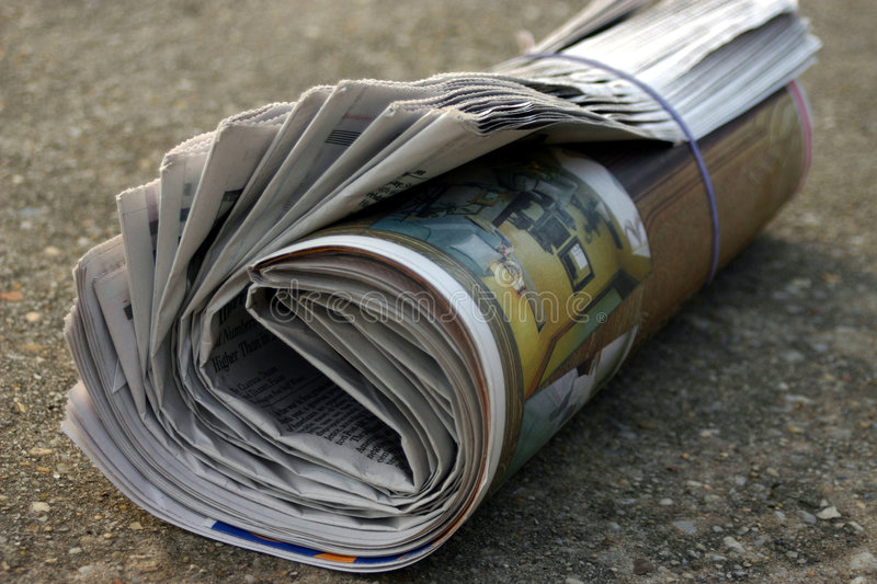 Rolled up newspaper stock photo