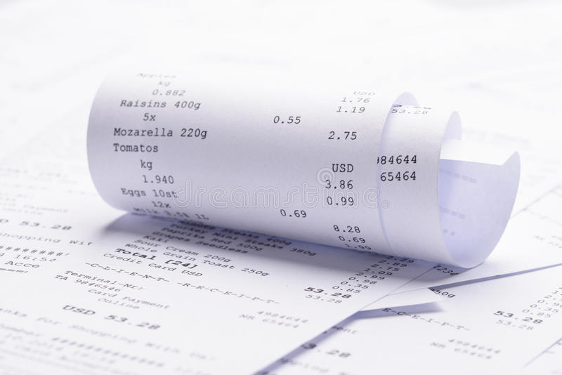 Rolled-up receipt with costs stock photography