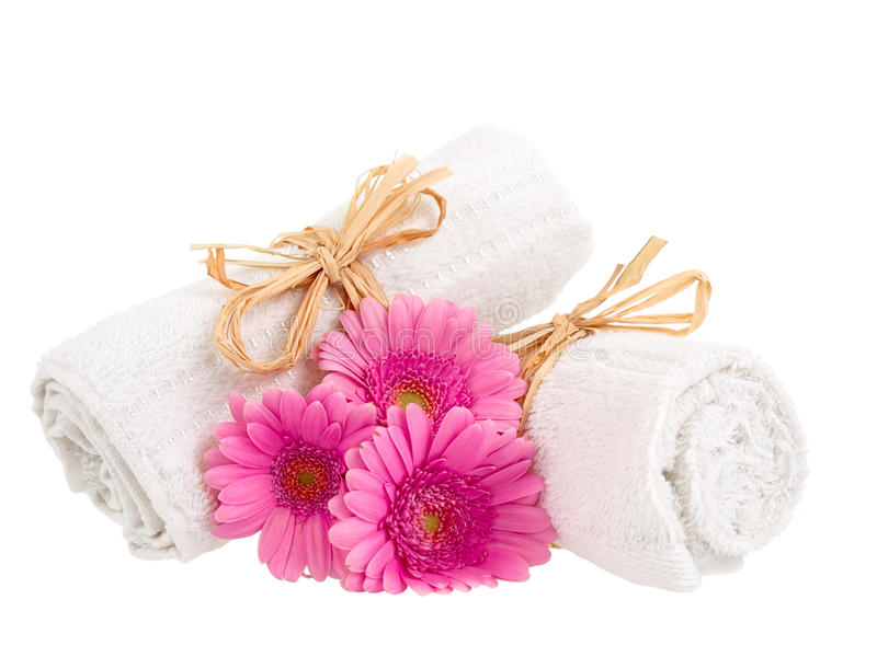 Rolled up towels with flowers. On pure white background royalty free stock photo