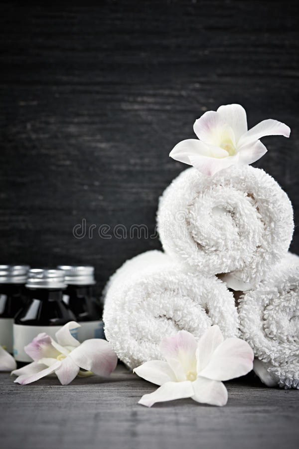 Rolled up towels and products at spa. White rolled up towels with body care products at spa stock photo