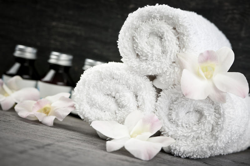 Rolled up towels and products at spa. White rolled up towels with body care products at spa royalty free stock images