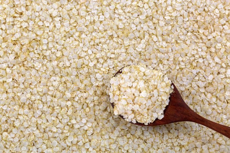 Rolled white Quinoa seed gluten-free flakes. Flattened organic grains high in protein, dietary fiber, B vitamins, dietary minerals stock images