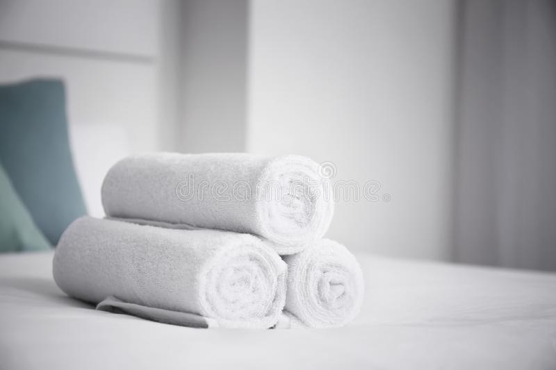 Rolled white towels on bed royalty free stock photography