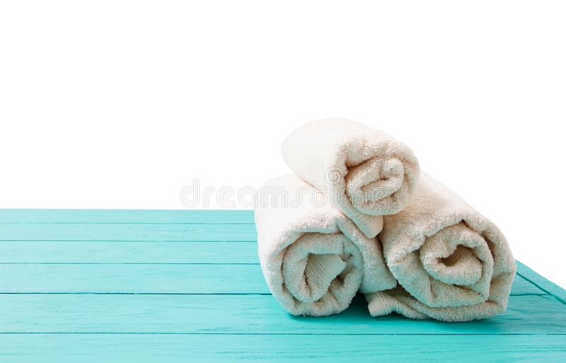 Rolled white towels on blue wooden table isolated on white background. Copy space and top view. Bathroom objects for shower body. Treatment. Selective focus stock images