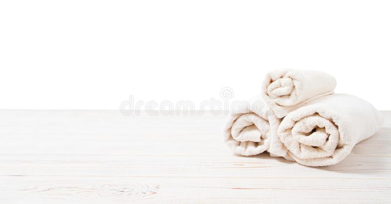 Rolled white towels on white wooden table isolated on white background. Copy space and top view. Bathroom objects for shower body stock photos
