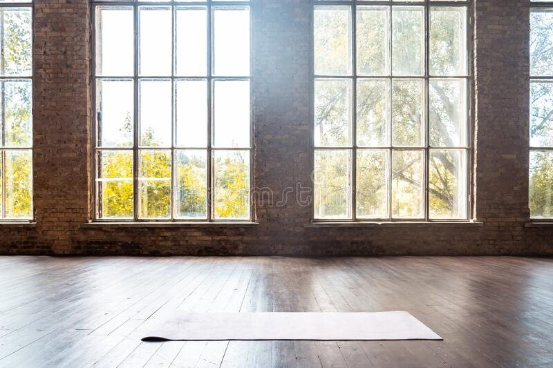 Rolled yoga pilates rubber mat inside gym studio on wooden floor background royalty free stock photography