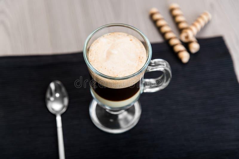 Rollen des Kaffees Bombon und der Oblate auf einer dunklen Serviette stockbilder