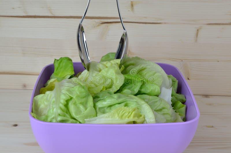 Rollen Sie mit frischem grünem Salat und Salatlöffeln stockfotografie