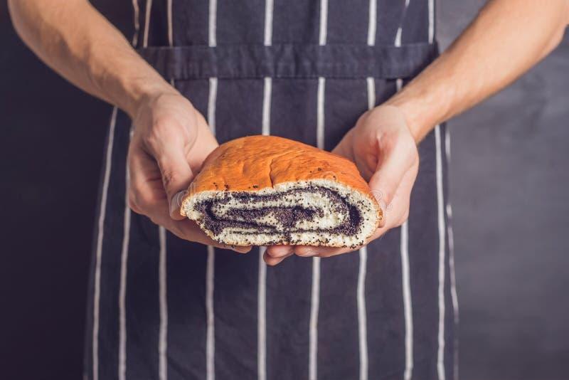 Rollen Sie mit Mohn in den Händen eines Bäckers lizenzfreies stockfoto