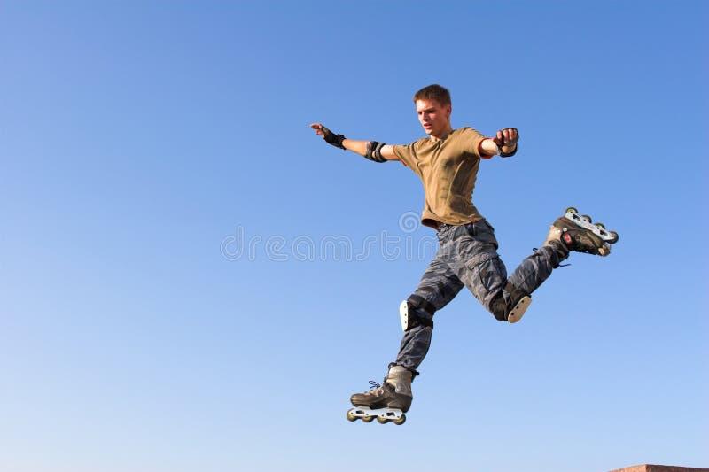 Rollenjunge, der vom Geländer auf dem blauen Himmel springt stockfotos