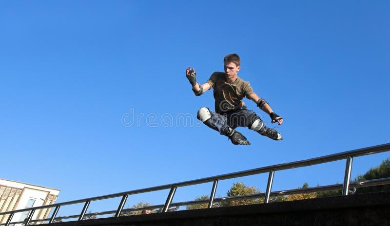 Rollenjunge, der vom Geländer springt lizenzfreie stockbilder