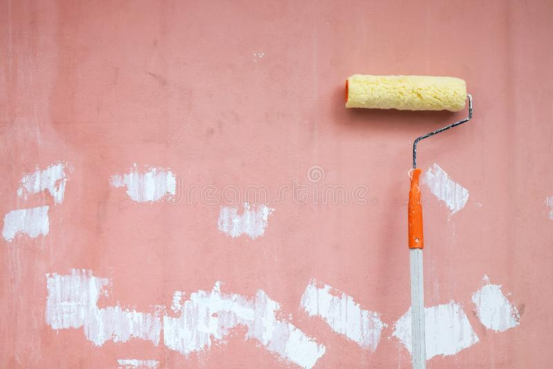 Rollenmalerpinsel-Lage auf dem Schmutz und schmutzige Wand bereiten sich für Col. vor lizenzfreie stockfotos