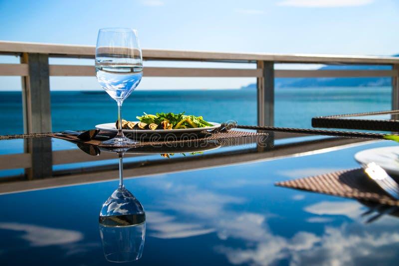 Rollensushisalat und Glas ruhiges Wasser stockbild