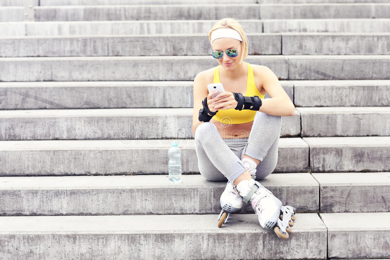 Roller blader using a cellphone royalty free stock photos