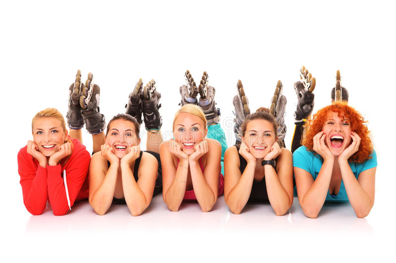 Roller blading. A picture of five girl friends resting over white background with their roller blades on stock images