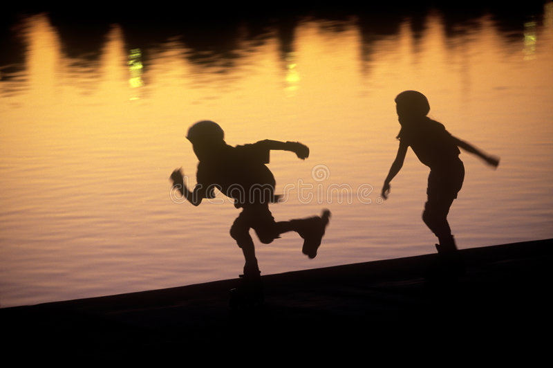 Roller Blading. Two kids roller blading next to a lake royalty free stock images