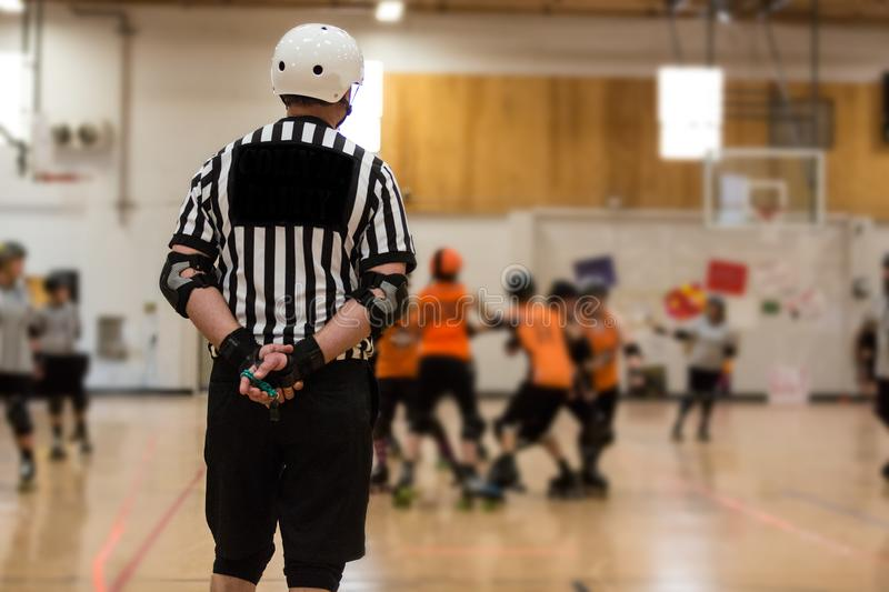 Roller derby referee watches team. S for penalties stock photos