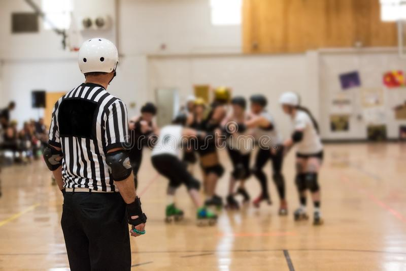Roller derby referee watches team. S for penalties royalty free stock image