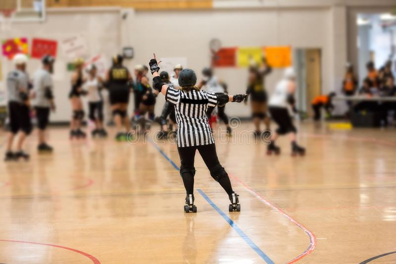 Roller derby referee watches team. S for penalties royalty free stock photos