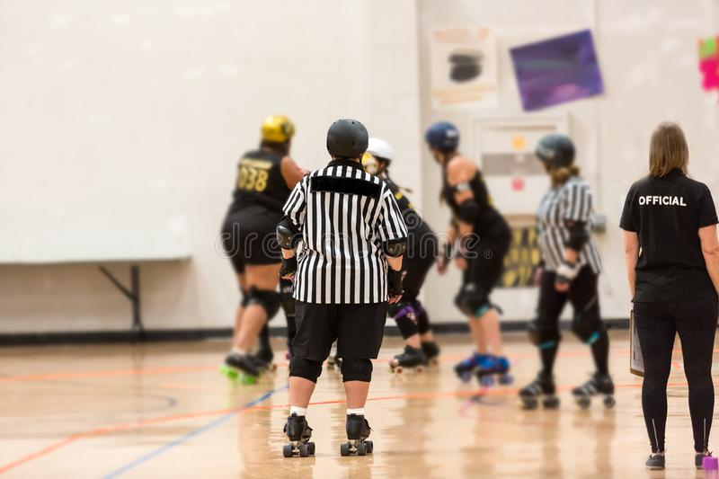 Roller derby referee watches team. S for penalties stock image