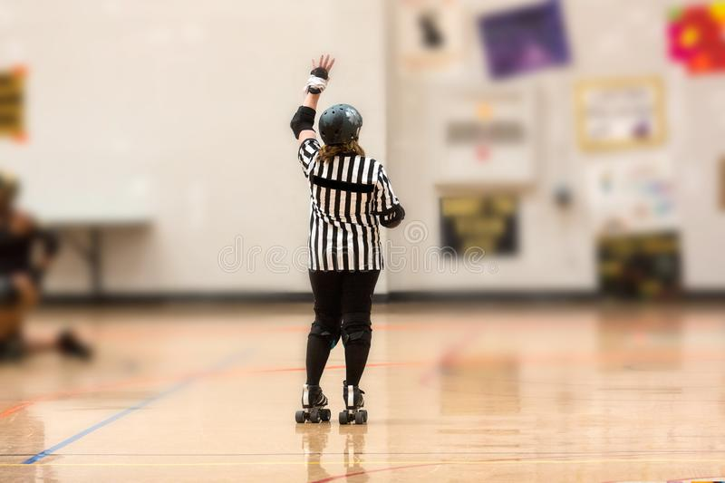 Roller derby referee watches team. S for penalties stock photography
