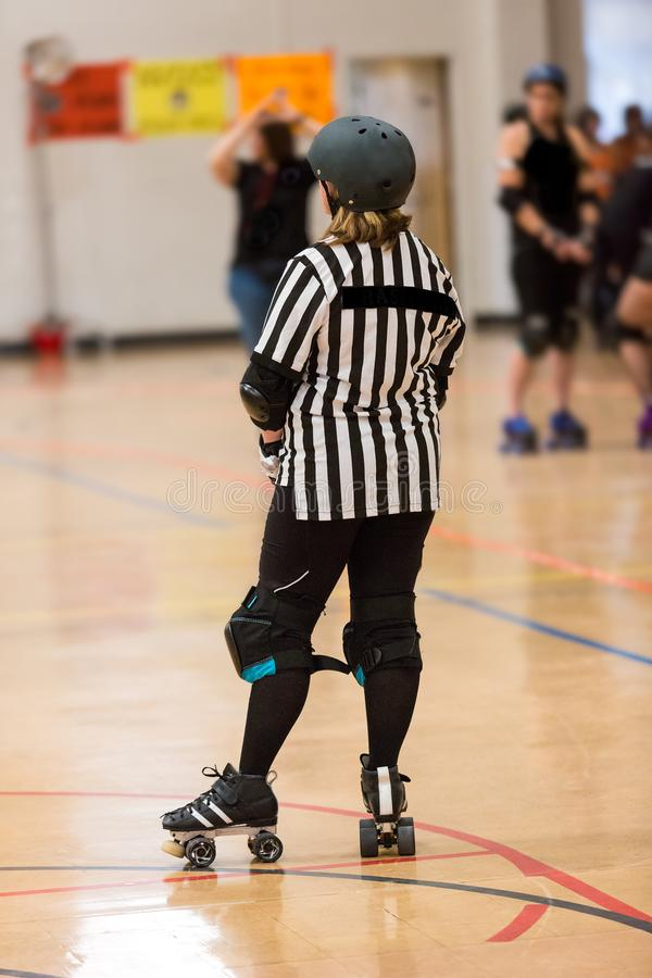 Roller derby referee watches team. S for penalties royalty free stock photo