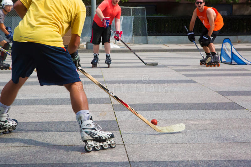 Roller in-line hockey in Washington downtown. Washington DC, USA - August 2015: Young men play roller in-line hockey outdoor in downtown. Two teams were playing stock image