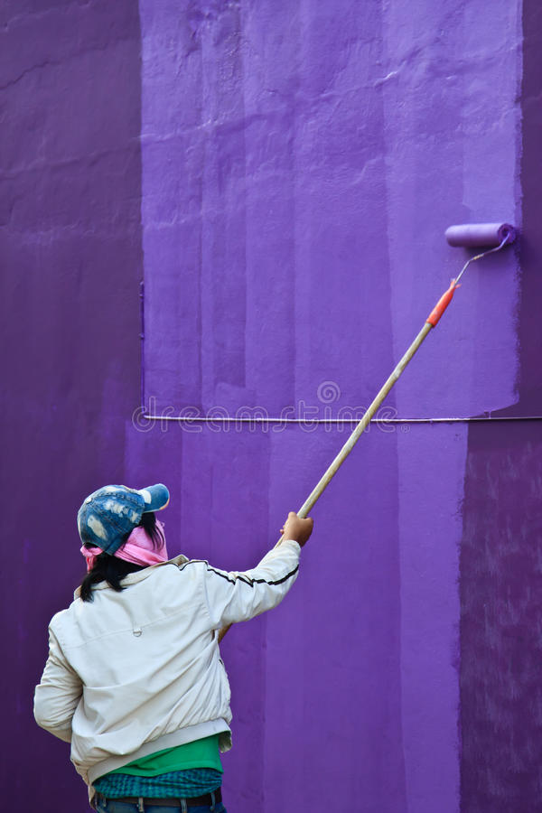 Roller painting wall on purple color. Violet purple wall human house painter stock photo