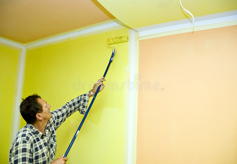 Roller painting in yellow stock photo