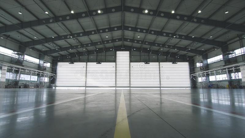 Roller shutter door and concrete floor inside factory building for industrial background. Airplane in front of half stock image