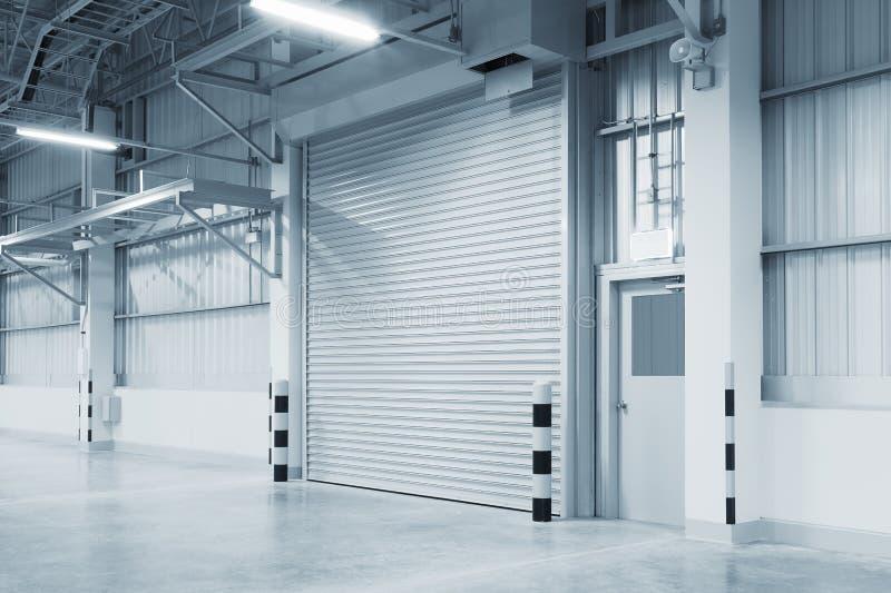 Shutter door factory. Roller shutter door and concrete floor inside factory building for industry background royalty free stock photography
