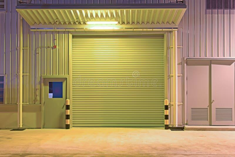 Shutter door factory. Roller shutter door and concrete floor outside factory building for industry background stock photos