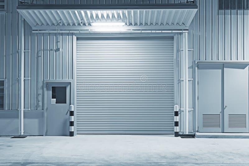 Shutter door factory. Roller shutter door and concrete floor outside factory building for industry background stock photo
