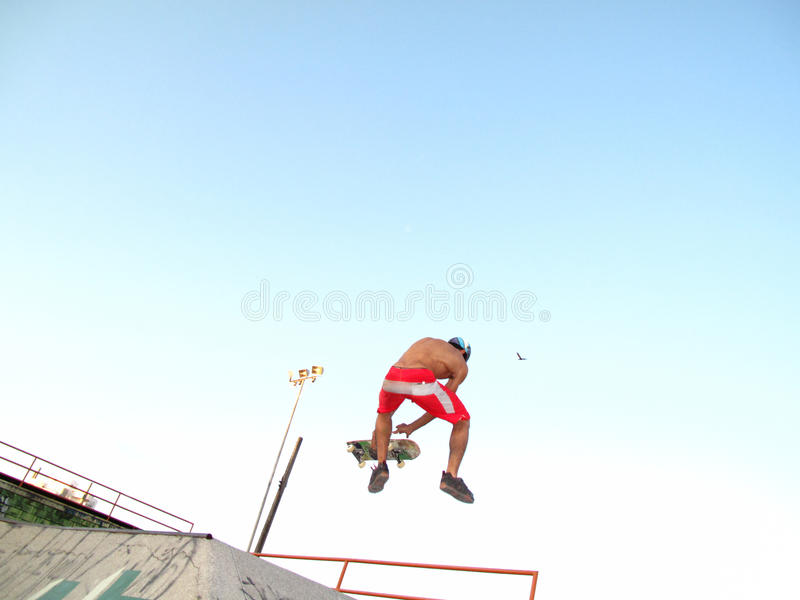 Roller skater jumping high with his skate board royalty free stock photo