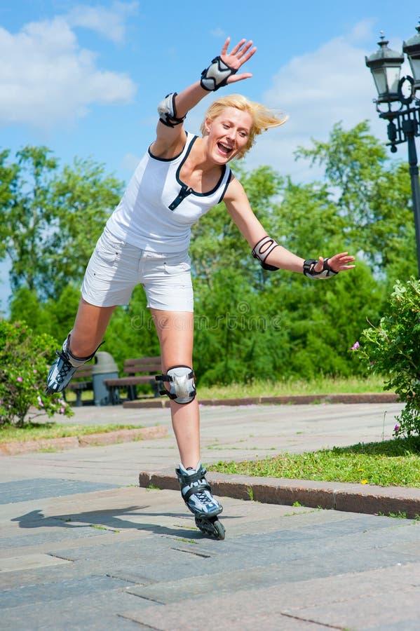 Roller-skating de fille en stationnement photographie stock