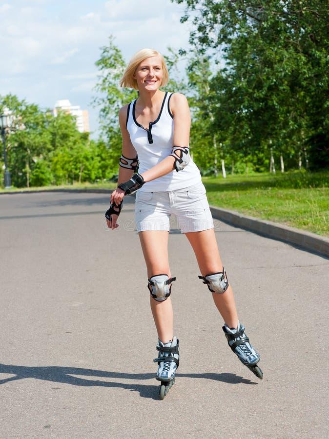 Roller-skating de la muchacha en el parque imágenes de archivo libres de regalías