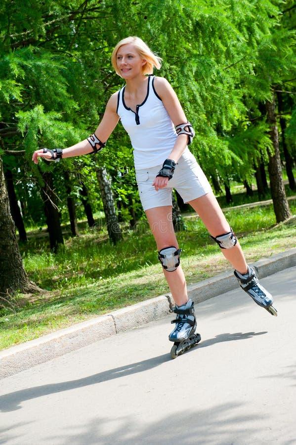 Roller-skating de la muchacha en el parque fotos de archivo