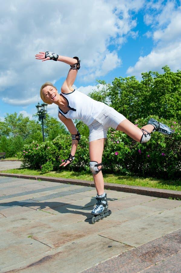 Roller-skating de la muchacha en el parque imagenes de archivo