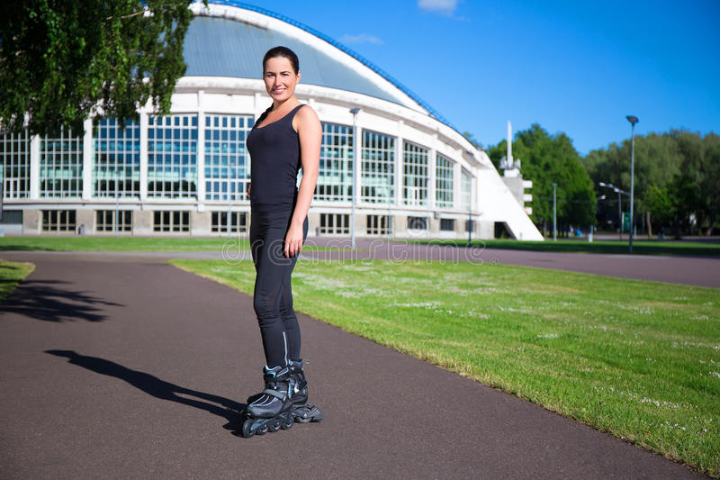 Roller skating girl in park rollerblading on inline skates stock photo