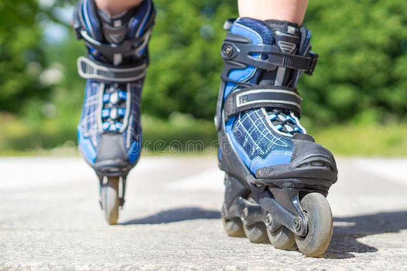 Roller skating in summer. Blue rollerskating on tarmac and asphalt on sunny day. Inline skating on asphalt in the city. Fun free time activity. Nature, trees royalty free stock photo