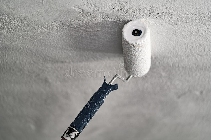 Roller with white paint on a concrete ceiling royalty free stock photos