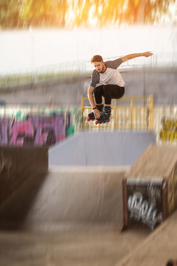 Rollerblader is jumping. Roller skater on blurred background. Defy the laws of gravity stock photo